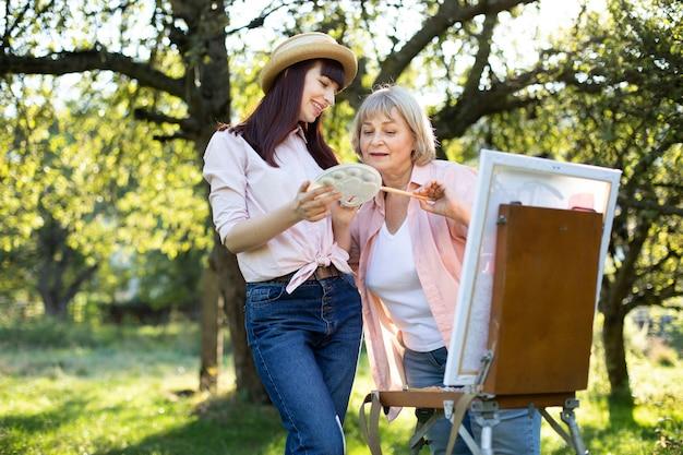 Schließen sie das outdoor-porträt einer 60-jährigen frau und ihrer kleinen tochter, die an einem sonnigen tag im garten zusammen mit der staffelei malen. ältere mutter und junge tochter, die eine farbe auf einer palette wählen.