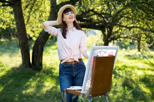 Schließen sie das outdoor-porträt einer jungen charmanten kaukasischen frau in strohhut, hemd und jeans, die in einem garten posiert, während sie ein bild auf leinwand malen.