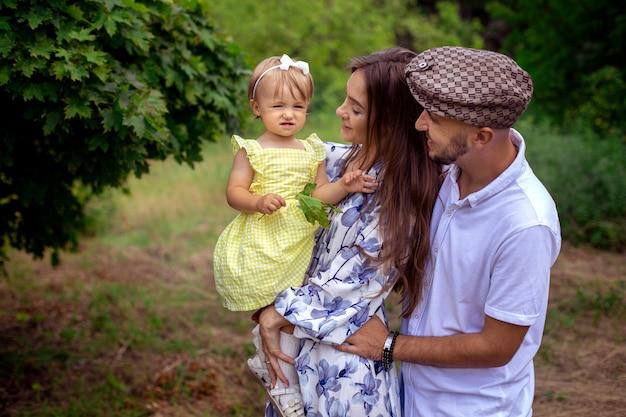 Schließen sie das porträt einer schönen jungen familie, die an einem warmen sommertag ein kleines, stilvolles baby im grünen park trägt