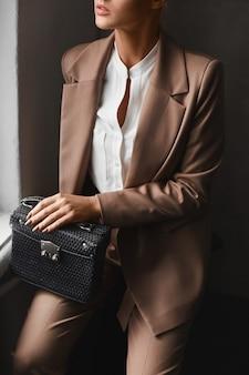 Schließen sie das porträt eines model-mädchens in einem modischen anzug, das mit einer trendigen handtasche am fenster posiert