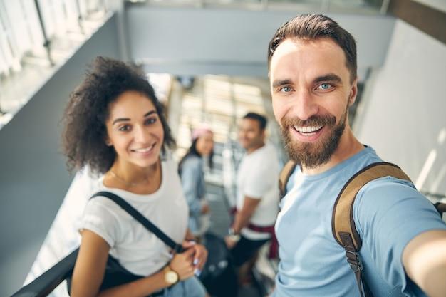 Schließen sie das porträt von glücklich lächelnden freunden mit rucksack auf den schultern, während sie die kamera ihres mobiltelefons betrachten