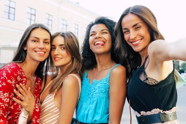 Schließen sie das selfie-foto von vier freundinnen im urlaub, die sommeroutfits tragen, in die kamera schauen, breit lächeln und die zunge herausstrecken.