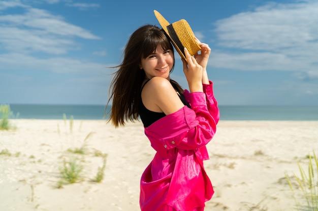 Schließen sie das sommerporträt einer modischen hübschen frau mit strohhut, die am tropischen strand posiert. rosa urlaubsoutfit tragen.