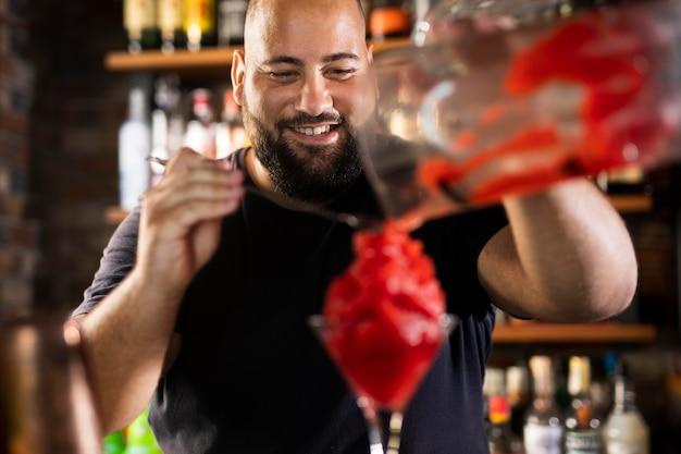 Schließen sie den barkeeper, der ein köstliches getränk kreiert