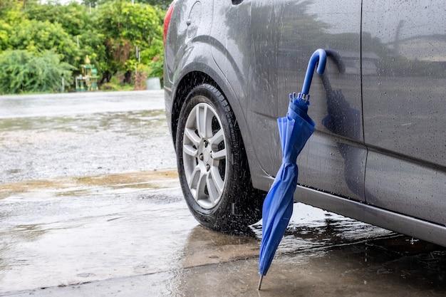 Schließen sie den blauen regenschirm, der mit grauem auto faltet