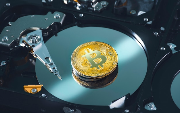 Schließen sie den goldenen bitcoin-platz auf der platte der festplatte im inneren, kryptowährungskonzept
