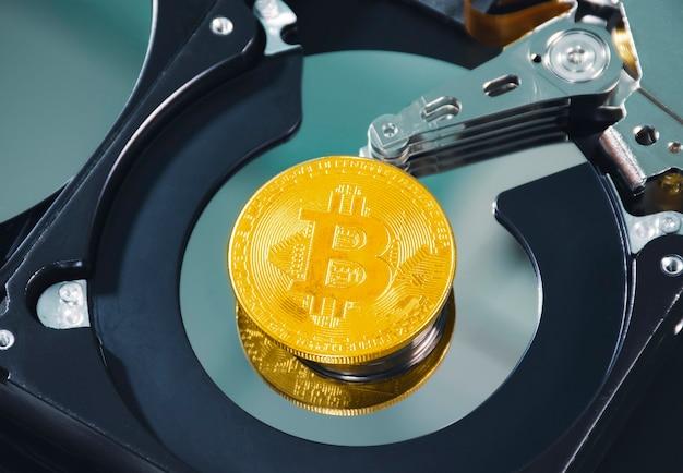 Schließen sie den goldenen bitcoin-platz auf der platte der festplatte im kryptowährungskonzept