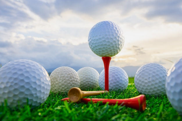Schließen sie den golfball auf t-stücken, die bereit sind zu spielen und auf grünem gras