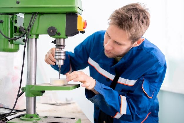 Schließen sie den jungen männlichen arbeiter mit einer bohrmaschine in der fabrik