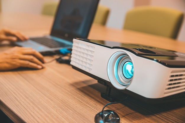 Schließen sie den projektor auf tischen im besprechungsraum
