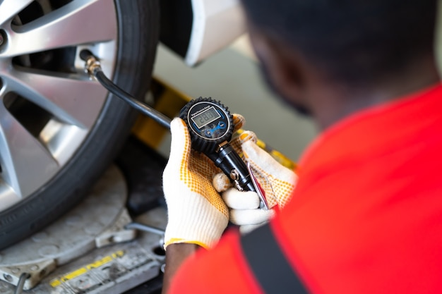 Schließen sie den schwarzen mechaniker, der einen reifen in der tankstelle aufpumpt. luftdruck mit manometer prüfen