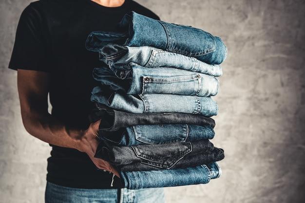 Schließen sie den stapel gefalteter jeans in der hand über grauem wandhintergrund, kopienraum