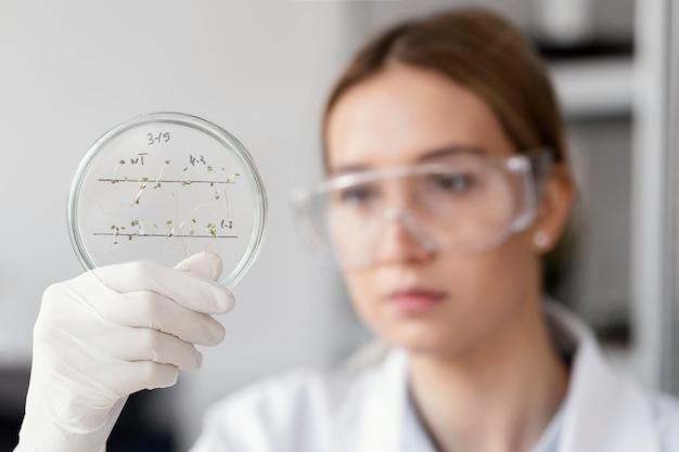 Schließen sie den verschwommenen wissenschaftler mit der schutzbrille