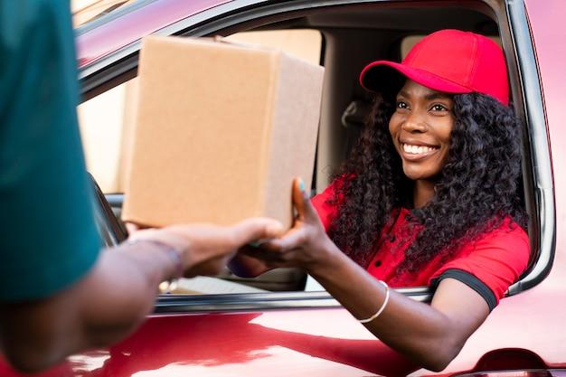 Schließen sie den zusteller, der dem kunden ein paket anbietet