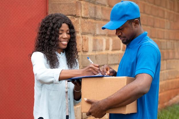 Schließen sie den zusteller, der dem kunden ein paket gibt