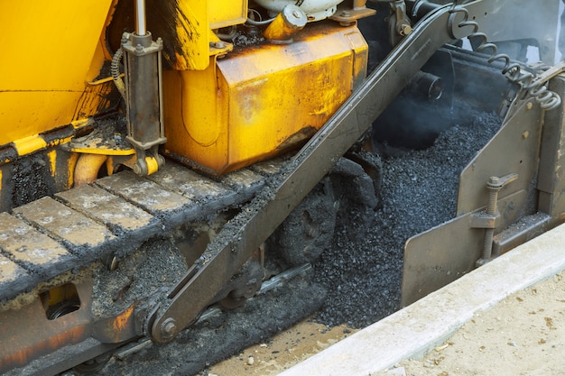 Schließen sie die arbeiter und die asphaltiermaschinen