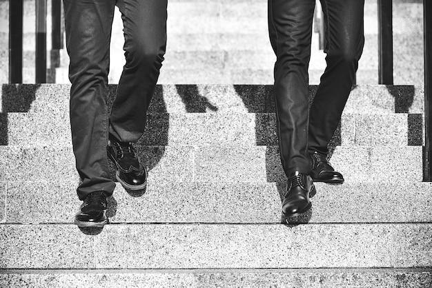 Schließen sie die beine von zwei geschäftsmann, die in der modernen stadt die treppe hinuntergehen
