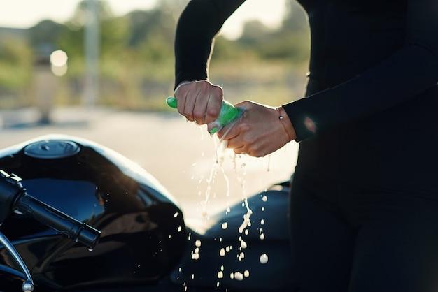 Schließen sie die hände der frau, drücken sie feuchtigkeit aus dem lappen, während sie das sportmotorrad bei der selbstbedienung abwischen