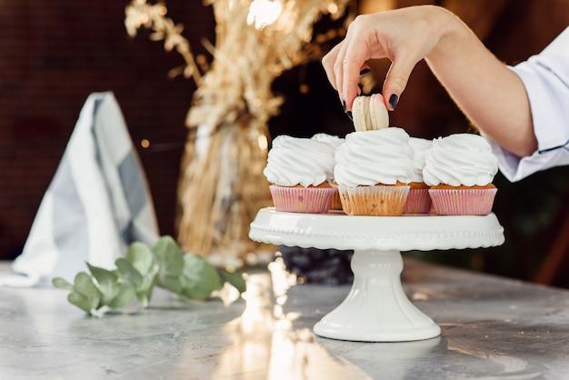 Schließen sie die hände der konditorin und legen sie einen frischen macaron mit sahne auf den cupcake.