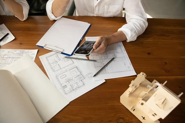 Schließen sie die hände des architekten-ingenieurs und des jungen paares während der präsentation des zukünftigen hauses. draufsichttabelle mit dokumenten, blaupause. erstes zuhause, industrie, gebäudekonzept. umzug in einen neuen live-ort.