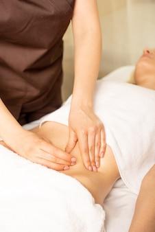 Schließen sie die hände des chiropraktikers oder masseurs, die entspannende magenmassage für liegende frau im klinikinneren machen.