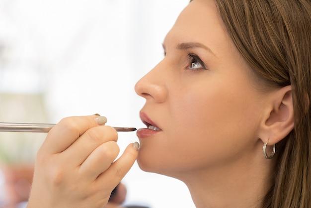 Schließen sie die hände des maskenbildners mit dem pinsel, der make-up auf eine hübsche frau anwendet