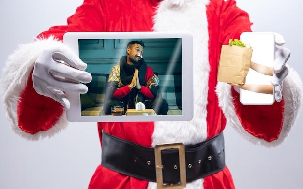 Schließen sie die hände des weihnachtsmanns, der das gerät mit den händen hält, die dem kranken mann auf dem bildschirm essen geben. konzept der lieferung, neujahr 2021 und weihnachtsfeier, gerät und gadgets, online-shopping.