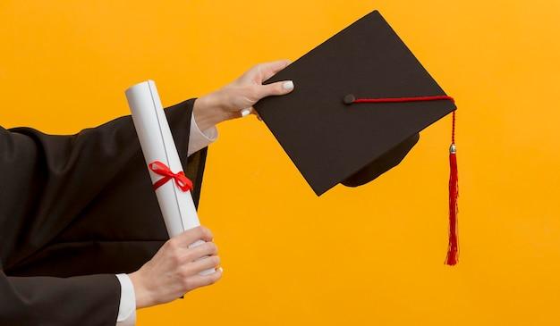 Schließen sie die hände, die diplom und kappe halten