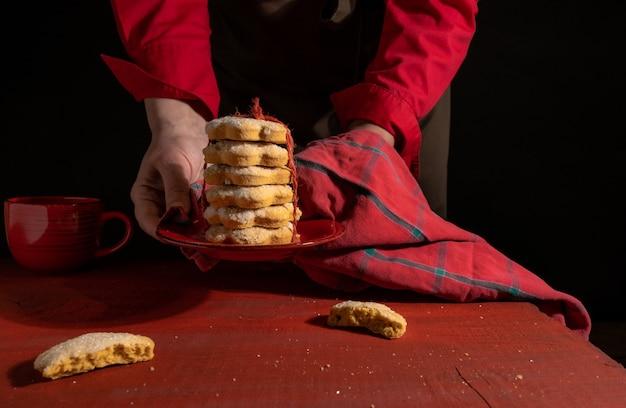 Schließen sie die hände, die hausgemachte kekse halten