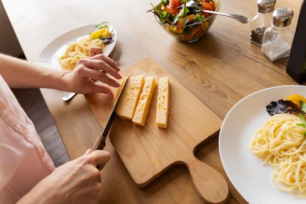 Schließen sie die hände, die käse schneiden