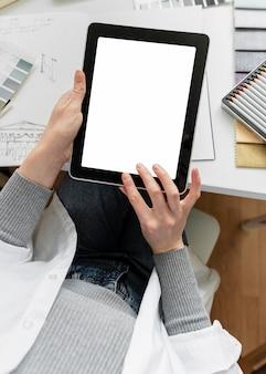 Schließen sie die hände, die mit tablette arbeiten