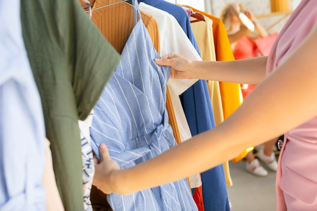 Schließen sie die hände, die stoff ausprobieren und nach neuer kleidung suchen.