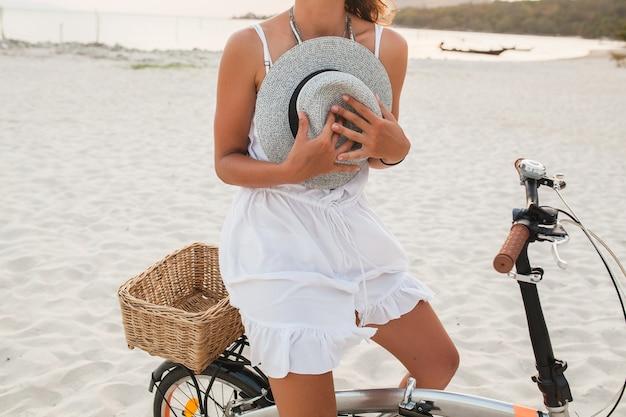 Schließen sie die hände, die strohhut der jungen attraktiven frau im weißen kleid halten, das auf tropischem strand auf fahrrad reitet