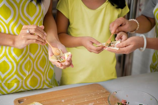 Schließen sie die hände, die zusammen kochen