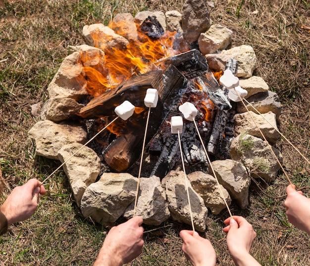 Schließen sie die hände mit marshmallows