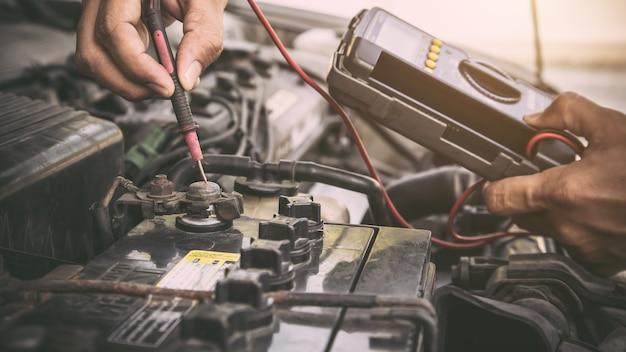 Schließen sie die hand des automechanikers mit dem messwerkzeug, das die autobatterie überprüft.