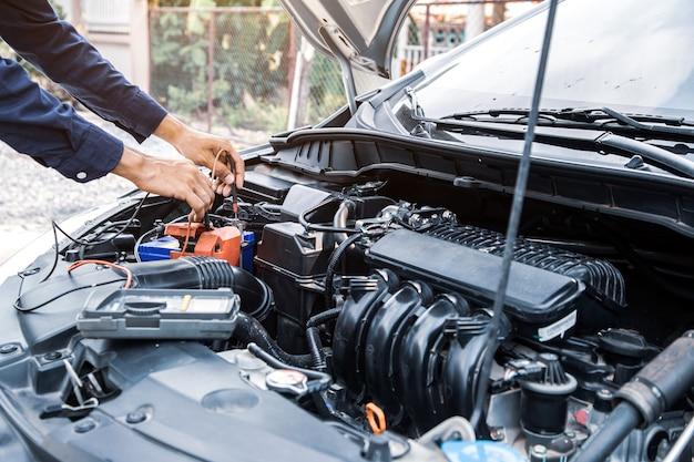 Schließen sie die hand des automechanikers mit der messung der autobatterie.