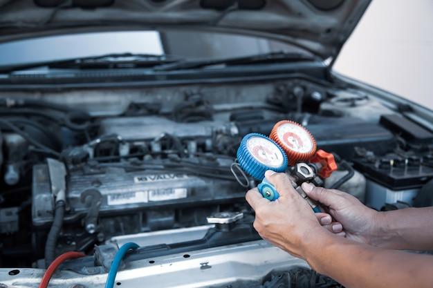 Schließen sie die hand des mechanikers mit der füllstandsanzeige für autoklimaanlagen