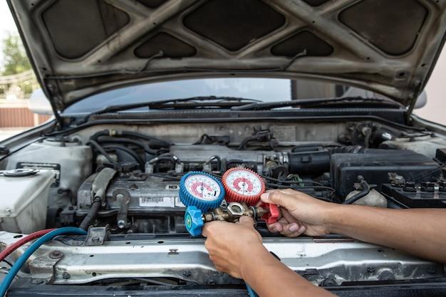 Schließen sie die hand des mechanikers mit der füllstandsanzeige für autoklimaanlagen.