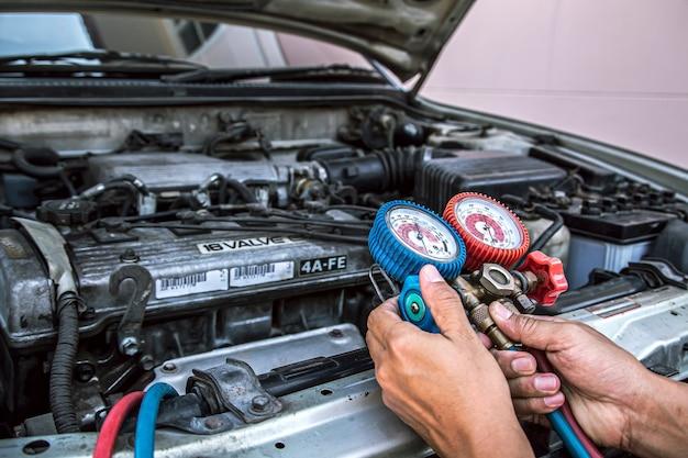 Schließen sie die hand des technikers, der das manometer verwendet, um autoklimaanlagen zu füllen.