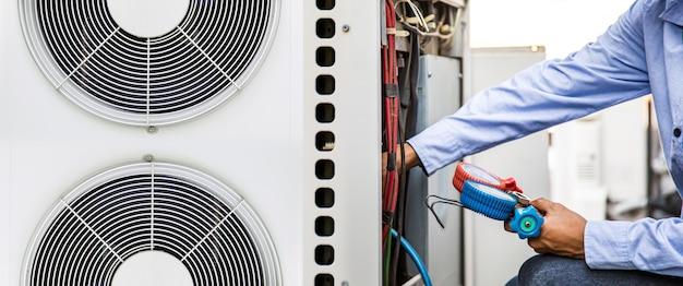 Schließen sie die hand des technikers, der das manometer zum befüllen von klimaanlagen verwendet.