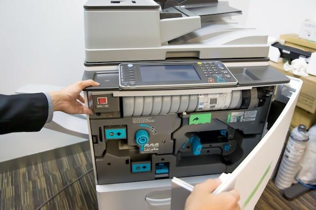 Schließen sie die hand des technikers, um die abdeckung des kopierers zu öffnen.
