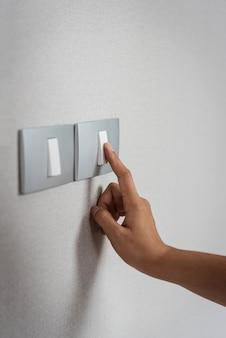Schließen sie die hand, die an grauen lichtschaltern mit beschaffenheitshintergrund ein- oder ausschaltet.