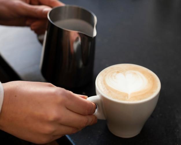 Schließen sie die hand, die tasse mit kaffee hält