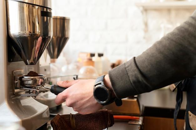 Schließen sie die hand mit der uhr, die kaffee zubereitet