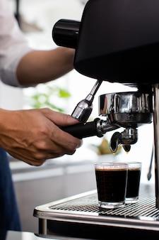 Schließen sie die hand. zubereitung einer tasse kaffee in einer kaffeemaschine, dampf und tasse. espressomaschine mit siebträger hautnah. konzept-kaffeemaschine im café.