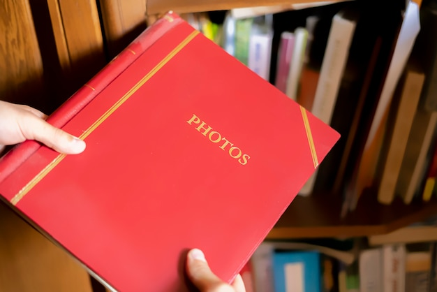 Schließen sie die handsuche und nehmen sie das rote fotoalbum in das bücherregal