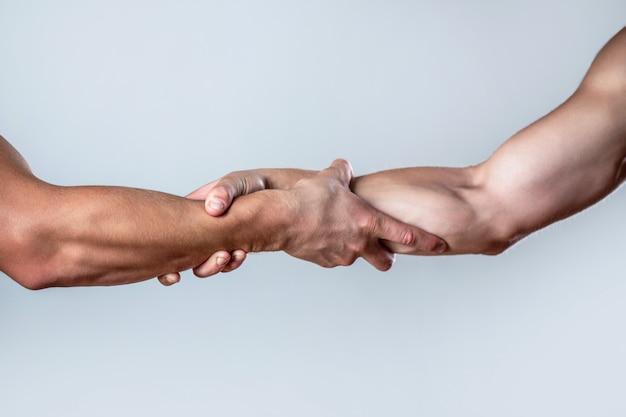 Schließen sie die hilfehand. zwei hände, helfender arm eines freundes, teamwork. helfende hand konzept und internationaler tag des friedens, unterstützung. nahansicht. helfende hand ausgestreckter, isolierter arm, erlösung.