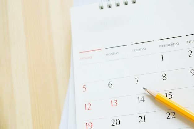 Schließen sie die seitenzahl des kalenders. bleistift gelb, um das gewünschte datum zu markieren und die erinnerung auf dem tisch zu erinnern.