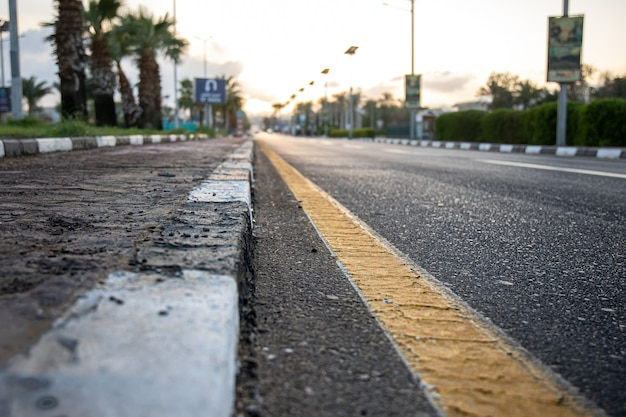 Schließen sie die stadtasphaltstraße mit palmen entlang der straße bei sonnenuntergang